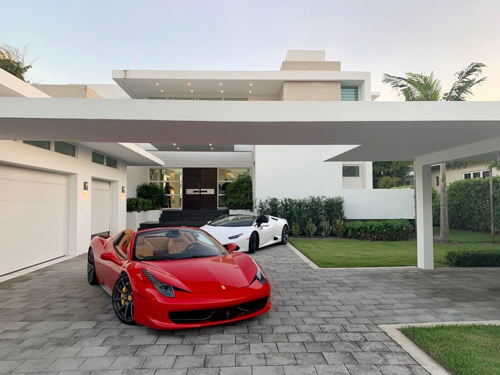 Florida Luxury home with Red Ferrari and White Lamborghini in front of house