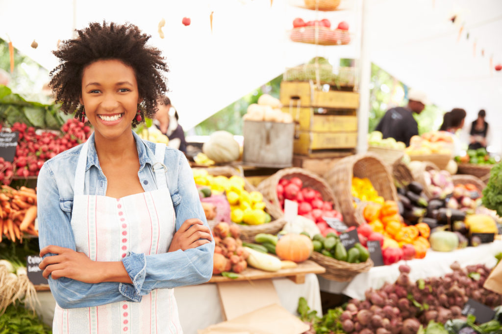 Smiling woman in front of large fruit stand at outdoor market